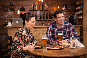 Couple relaxing at pub and eating pizza. They are laughing and eating pizza.