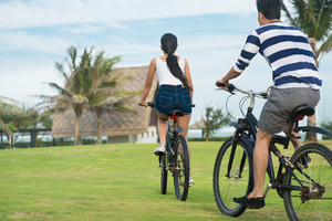 Couple riding on bicycles outdoors, rear view