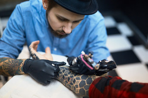 Creative adornment being drawn by professional tattooer