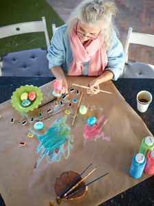 Creative aged woman painitng eggs with special paints
