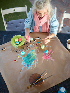 Creative grandparent painting Easter eggs by table