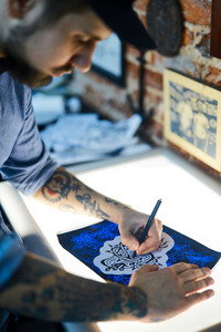 Creative man drwaing picture of tattoo
