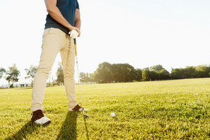 Cropped image of a golfer getting ready to put golf ball on green outdoors