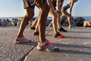 Cropped image of a group of people in sportswear ready to start a run outdoors