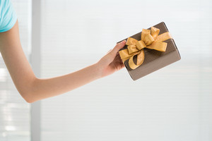Cropped image of a human hand holding a giftbox