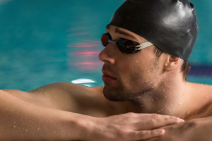 Cropped image of a male swimmer wearing goggles and swimming cap resting on the edge of a swimming pool and looking away