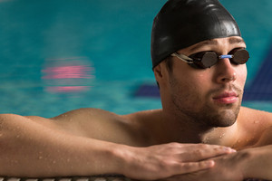 Cropped image of a male swimmer wearing goggles and swimming cap resting on the edge of a swimming pool