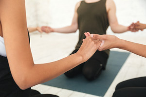 Cropped image of a male yoga instructor sitting in a circle with a group of women and holding hands meditating in a gym