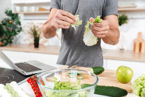 Cropped image of a man cooking salad in the kitchen with laptop