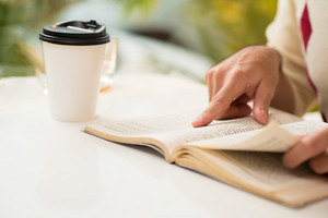 Cropped image of a person reading in the morning while drinking espresso coffee on the foreground