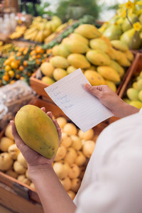 Cropped image of a woman shopping in the market according the shopping list