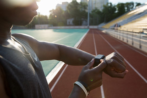 Cropped image of a young african athlete using wrist smartwatch at the stadium