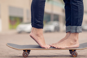 Cropped image of a young couple standing on the skateboard outside