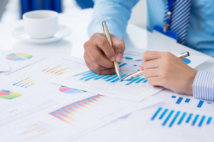 Cropped image of businesspeople analyzing financial graphs on the foreground
