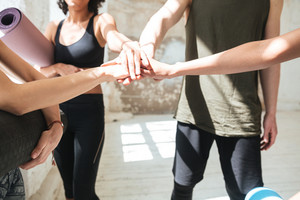 Cropped image of group of healthy pretty people making team gesture while doing yoga in gym