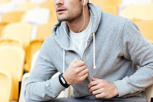 Cropped image of handsome young sports man at the stadium outdoors listening music.