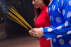 Cropped image of man and woman in ao dai dresses holding incense sticks
