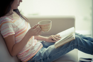 Cropped image of woman sitting on the sofa and reading a book at home