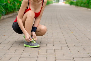 Cropped image of woman tying shoelaces before jogging