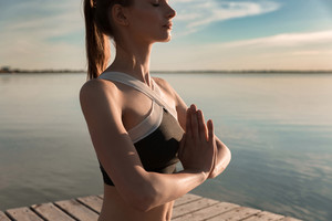 Cropped image of young sports lady at the beach make meditation exercises.