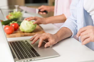 Cropped photo of mature loving couple family standing at the kitchen using laptop computer and cooking salad