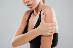 Cropped picture of a fitness woman with pain in her shoulder over gray background