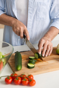 Cropped picture of mature attractive man standing at the kitchen cooking salad.