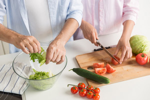 Cropped picture of mature loving couple family standing at the kitchen cooking.