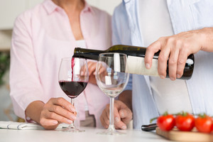 Cropped picture of mature loving couple family standing at the kitchen drinking wine