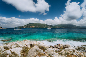 Crystal clear transparent blue turquoise teal Mediterranean sea water in Fiskardo town. White yacht in open sea at anchor under amazing white clouds, Kefalonia, Ionian islands, Greece
