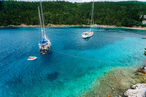 Crystal clear transparent blue turquoise teal mediterranean sea water of Foki Fiskardo Beach with some white yacht in the bay, Kefalonia, Ionian islands, Greece