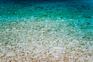 Crystal clear turquoise waters, peaceful bay with calm transparent water surface. Idyllic Summer vacation consept, Greece