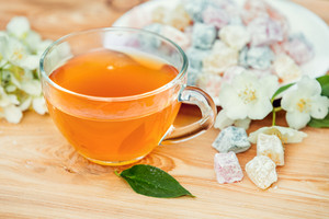 Cup of green tea with jasmine decorated with a turkish delight on wooden table