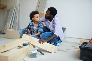 Cute boy talking to father while drilling wooden plank during house renovation