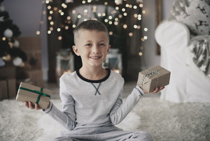 Cute boy with gifts looking at camera