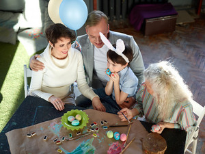 Cute bunny boy with two painted eggs, his parents and granny sitting by table