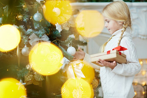 Cute child with package looking at xmas bubble hanging on decorated firtree