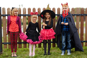 Cute friendly children in Halloween costumes
