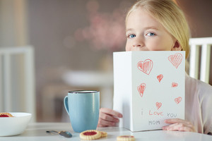 Cute girl peeking out of greeting card for her mother