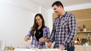 Cute joyful couple cooking together and spending time together. Happiness