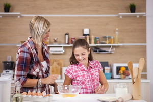 Cute little girl and her mother cooking something delicious. Baking desert,