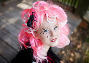 Cute little girl in pink wig looking at camera