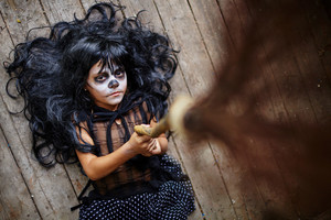 Cute little girl with broom lying on wooden floor