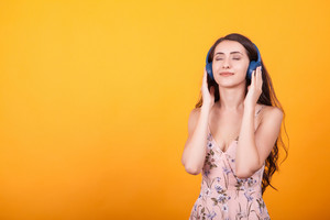 Cute young woman listening music in studio from her headpshones on yellow background.