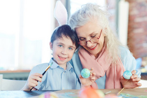 Cute youngster looking at camera while painting Easter eggs with his granny near by