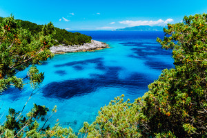 Dafnoudi beach in Kefalonia, Greece. Remote lagoon with pure crystal clean turquoise sea water, surrounded by cypress trees and white rocks
