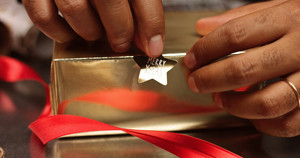 Dark skinned man's hands putting Merry Xmas sticker on a present with golden wrapping paper