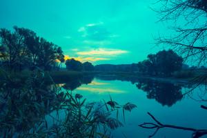 Dawn over the lake. Calm lake before sunrise. Rural landscape