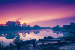 Dawn over the lake in misty morning. Calm lake before sunrise