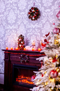 Decorated Christmas tree in front of the fireplace with various candles. Lovely mood.